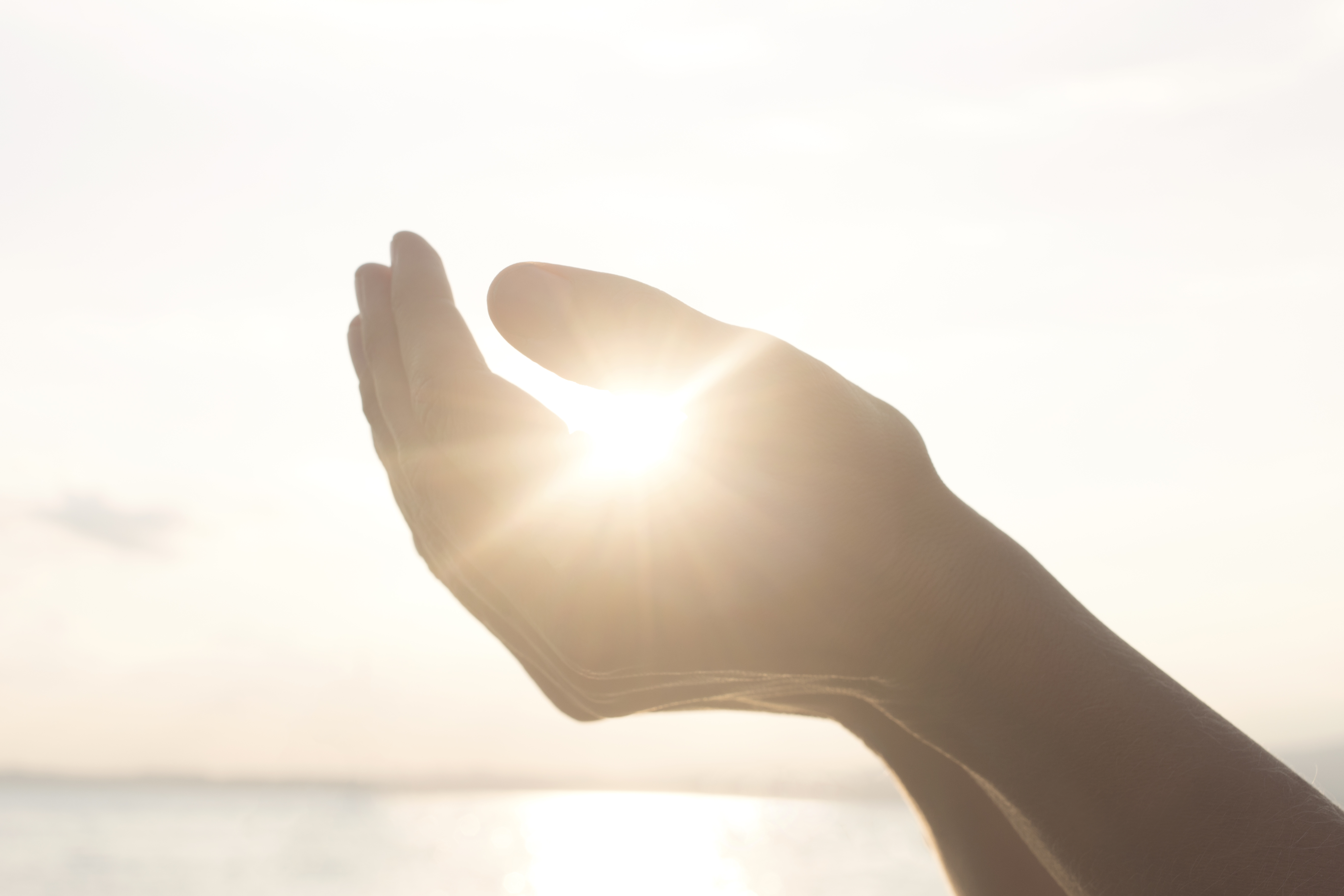 woman's hands hold the sun and its energy